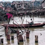 A man paddles a canoe past demolished stilt houses at Makoko in Lagos, Nigeria. The government recently forced thousands of evictions, and may have many more planned.