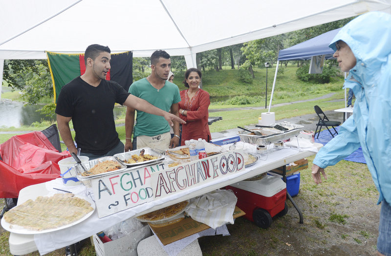 Sadiq Majeed, left, his brother Sameer Majeed and their mother, Hooria Majeed, talk with Susan Adler of Portland about the Afghan food the family is serving at the Festival of Nations in Deering Oaks park on Sunday. The Majeeds moved to Portland from Afghanistan in 2002.