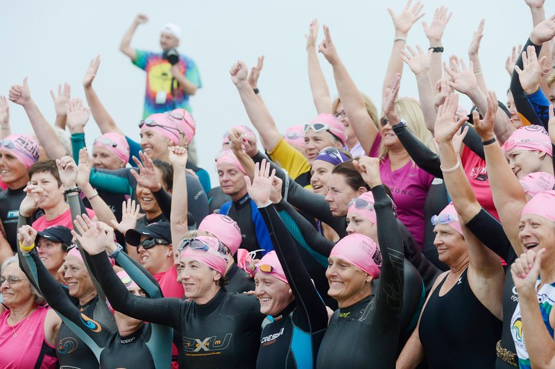 Cancer survivors pose for photos before the start of the Tri for a Cure on Sunday.