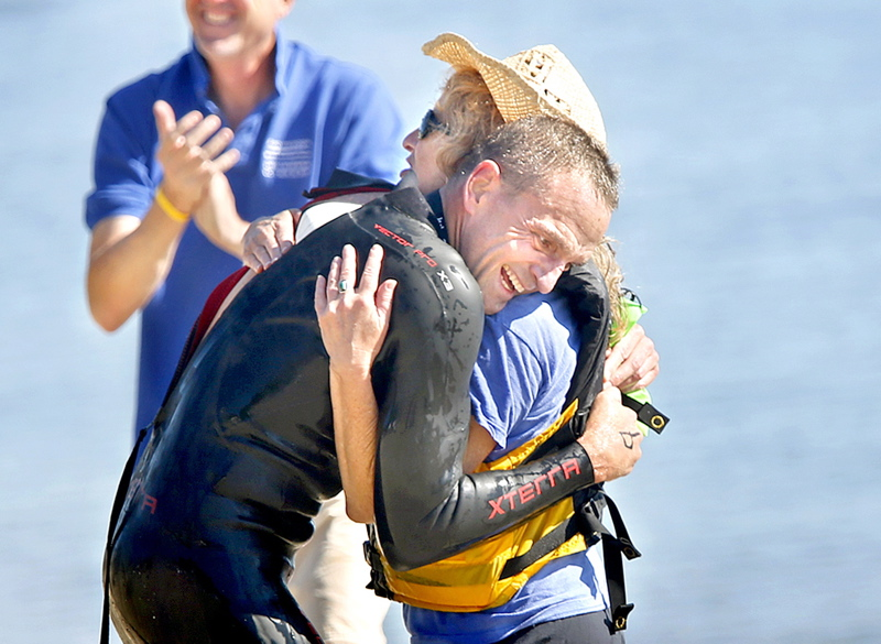 Scott Yeomans of Bethlehem, Pa., embraces his spotter and cousin Beth Ansheles of South Portland after winning the Peaks-to-Portland swim for the second straight year.