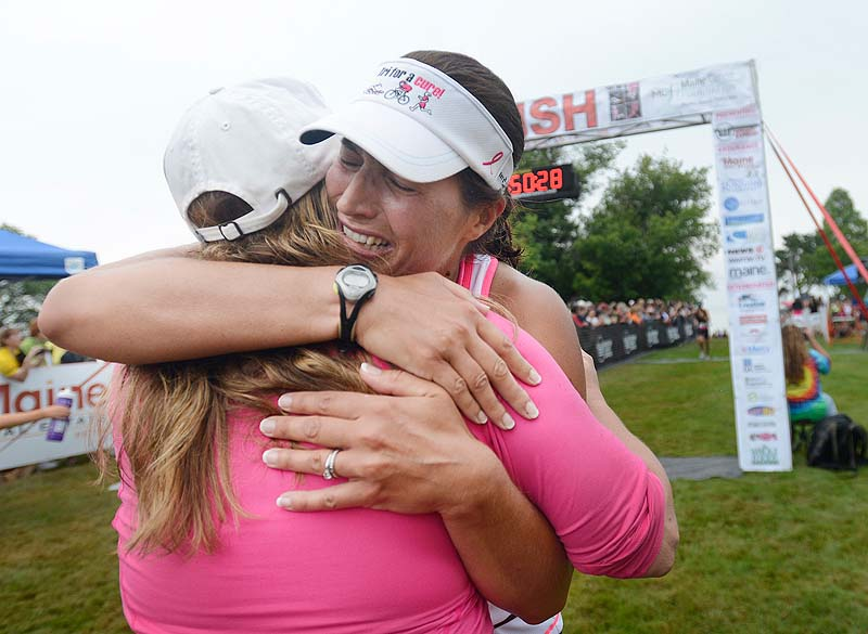 Sharon Leddy-Smart of South Portland, a breast cancer survivor, cries as she is greeted at the finish line by her cousin, Samantha Smith of Falmouth, who was recently diagnosed with cancer.