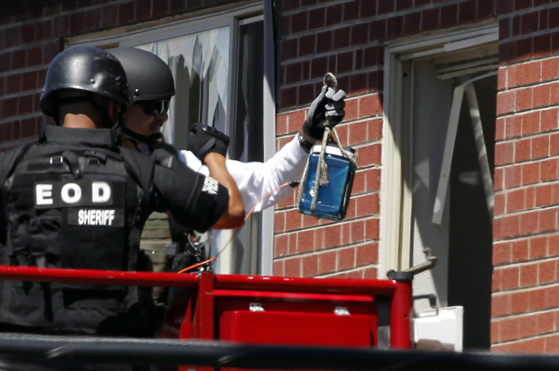 """Members of law enforcement wearing body armor and helmets prepare to what ATF sources describe as a""""water shot"""" in the apartment of alleged gunman James Holmes today. The """"water shot"""" is exploded and used to disrupt the device."""