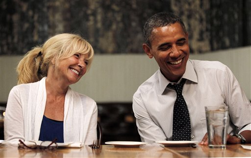 President Barack Obama, right, sits with Rose Oakleaf, left, at Mintwood Place restaurant in the Adams Morgan neighborhood in Washington, during dinner with winners of a campaign contest, Monday, Aug. 20, 2012. (AP Photo/Pablo Martinez Monsivais)