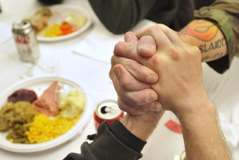 Homeless veterans join hands while attending a special dinner at Portland's Boys and Girls Club in December 2010. It's important to maintain a position at the Oxford Street Shelter to help this population.