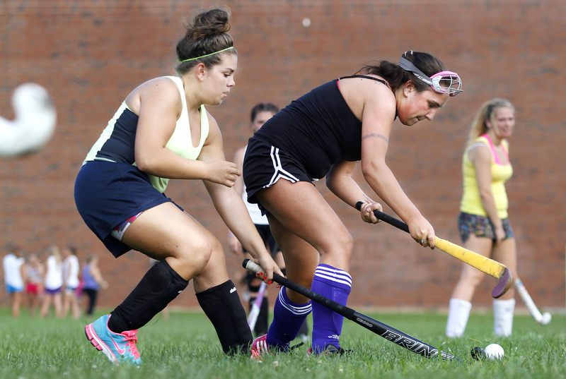 Kiana DiBiase, left, and Maya Hanna battle for the ball during Deering's opening field hockey practice.