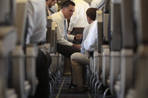 Republican presidential candidate, former Massachusetts Gov. Mitt Romney speaks to traveling press secretary Rick Gorka on the campaign charter flight before departure from Port Columbus International airport, Wednesday, Aug. 15, 2012, in Columbus , Ohio. (AP Photo/Mary Altaffer)