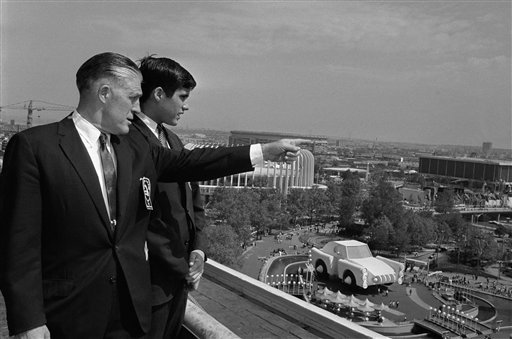FILE - In this May 18, 1964, file photo Gov. George Romney and his son, Mitt, look out over the New York World's Fair grounds from the heliport after attending a Michigan breakfast at the Top of the Fair Restaurant. The governor and a large delegation from Michigan are here for Michigan Day at the fair. At right is part of the Chrysler exhibit and behind them is the Ford exhibit. Long before Mitt Romney became the millionaire candidate from Massachusetts, he was his father' son, who idolized the outspoken, no-nonsense, auto executive turned politician. (AP Photo, File) politician;visit;world's;fair;view;pointing;father;son