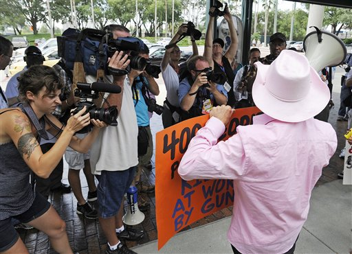 Photographers work as a Code Pink demonstrator speaks at a venue where former Secretary of State Condoleezza Rice was to speak, Tuesday, Aug. 28, 2012, in Tampa, Fla. Protestors gathered in Tampa to march in demonstration against the Republican National Convention. (AP Photo/Mike Stewart)