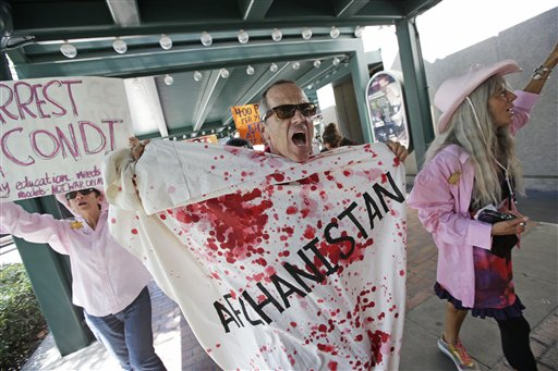 A Code Pink demonstrator chants at a venue where former Secretary of State Condoleezza Rice was to speak, Tuesday, Aug. 28, 2012, in Tampa, Fla. Protestors gathered in Tampa to march in demonstration against the Republican National Convention. (AP Photo/Dave Martin)