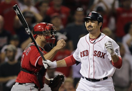 Boston Red Sox's Adrian Gonzalez, right, reacts as he strikes out swinging to end the game Thursday night. The Red Sox are close to trading Gonzalez, Josh Beckett and Carl Crawford to the Dodgers in a blockbuster deal. (AP Photo/Charles Krupa)