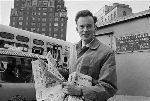 In this May 4, 1964 file photo, Malcolm Browne, then Associated Press correspondent in Vietnam, home on leave, reads New York newspapers at a newsstand near his parents' residence in New York following his Pulitzer Prize award. Browne, acclaimed for his trenchant reporting of the Vietnam War and a photo of a Buddhist monk's suicide by fire that shocked the Kennedy White House into a critical policy re-evaluation, died Monday night, Aug. 27, 2012 at a hospital in New Hampshire, not far from his home in Thetford, Vt. He was 81. (AP Photo)