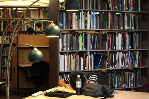 Taewon Kim, an electrical engineering systems graduate student, naps in the library on the campus of the University of Michigan, in Ann Arbor, Mich.