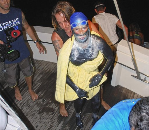 Diana Nyad is aided after she was pulled out of the water between Cuba and the Florida Keys early Tuesday, ending her fourth bid to swim from Cuba to Florida after four days of storms, jellyfish stings and shark threats.