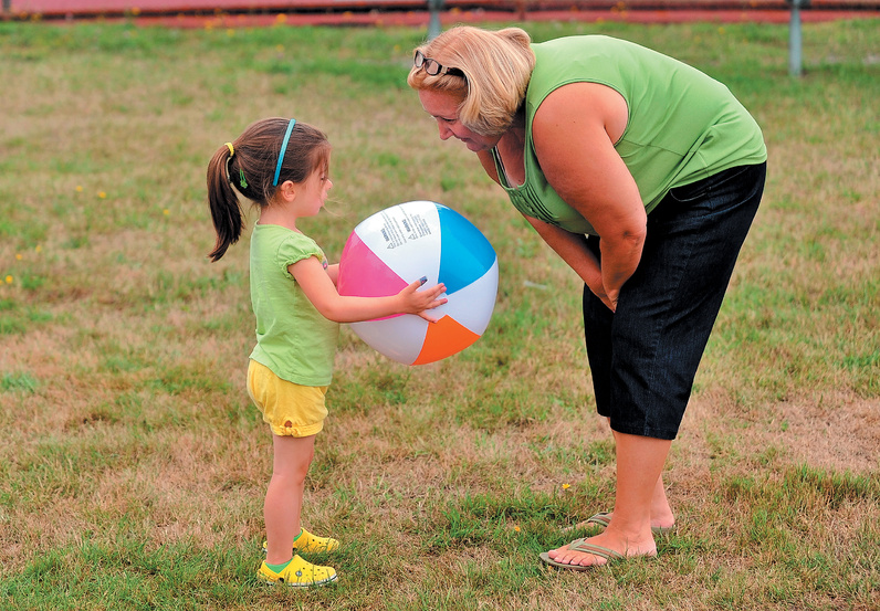 Nora Taylor, 3, looks to her grandmother Tina Couturier to play with a beach ball during the Family Fun Day.