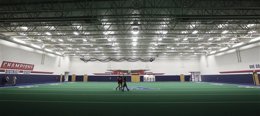 Students walk across the new indoor practice field that is part of the new $60 million football stadium at Allen High School.