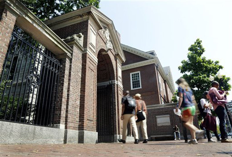 Pedestrians walk through a gate on the campus of Harvard University in Cambridge, Mass., on Thursday.
