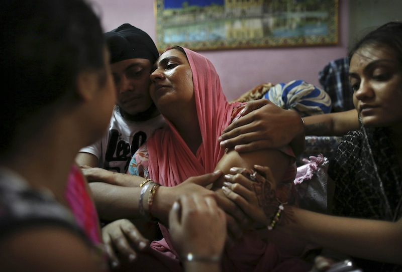 Indian Surinder Kaur, center, the wife of Seeta Singh who was killed in the shooting attack at a Sikh temple in Wisconsin, is comforted by her son Armeet and daughter Sarabjit, right, at the family home in New Delhi, India, Tuesday, Aug. 7, 2012. Singh was killed alongside his brother Ranjeet Singh who he had recently joined in the United States during the attack on Sunday. (AP Photo/Kevin Frayer)