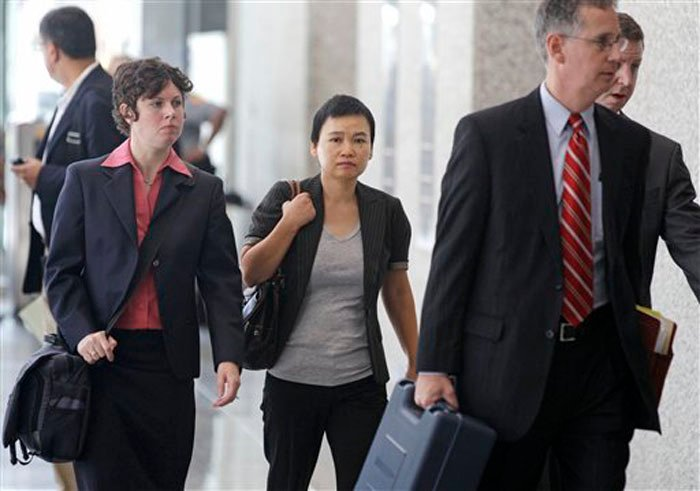 Hanjuan Jin, center, leaves the federal courthouse Wednesday, Aug. 29, 2012, in Chicago, after being sentenced to four years in prison for stealing trade secrets from Motorola. Jin, who worked as a software engineer for Motorola Inc. for nine years, was stopped during a random security search at Chicago's O'Hare International Airport on Feb. 28, 2007, before she could board a flight to China. Prosecutors say she was carrying $31,000 and hundreds of confidential Motorola documents, many stored on a laptop, four external hard drives, thumb drives and other devices. (AP Photo/M. Spencer Green)