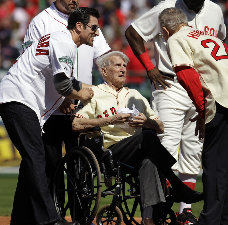 In this April 20, 2012, file photo, Boston Red Sox great Johnny Pesky, center, is greeted by former player Nomar Garciaparra, left, and others during a celebration of the 100th anniversary of the first regular-season baseball game at Fenway Park prior to the Red Sox taking on the New York Yankees in Boston. Pesky, who spent most of his 60-plus years in pro baseball with the Red Sox and was beloved by the team's fans, has died on Monday, Aug. 13, in Danvers, Mass. He was 92. (AP Photo/Elise Amendola, File)