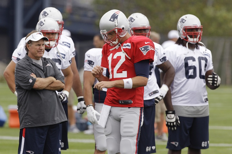 New England Patriots coach Bill Belichick looks over his practice field as quarterback Tom Brady (12) walks by during the first day of the NFL football team's training camp in Foxborough, Mass., Thursday, July 26, 2012. (AP Photo/Stephan Savoia)