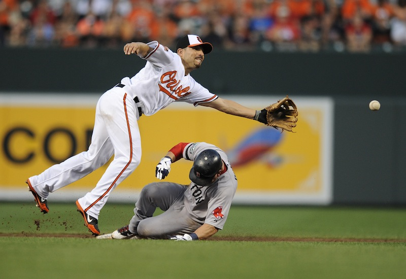 Boston Red Sox's Nick Punto, bottom, is slides safely into second on a wild pitch as Baltimore Orioles second baseman Omar Quintanilla, top, reaches for the ball during the second inning of a baseball game on Thursday, Aug. 16, 2012, in Baltimore. (AP Photo/Nick Wass)