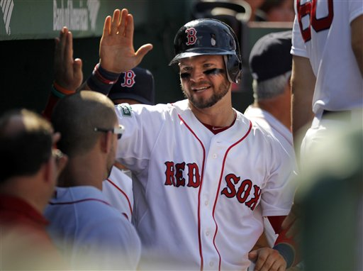 Boston Red Sox's Cody Ross, center, celebrates in the dugout after scoring on an RBI single Red Sox's James Loney in the sixth inning of a baseball game against the Kansas City Royals at Fenway Park, Monday, Aug. 27, 2012, in Boston. The Red Sox won 5-1. (AP Photo/Steven Senne)