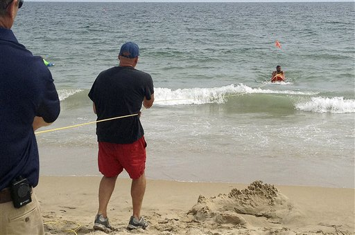 Fire Chief Louis Misto, far left, and lifeguard Jeff Lenihan, center, demonstrate a rescue technique with the EMILY remote-control lifesaving device as lifeguard Philip Campo, in water at right, holds on to the apparatus at Old Town Beach, in Westerly, R.I.