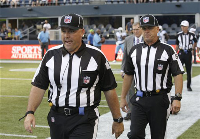 This Aug. 11, 2012 file photo shows replacement officials taking the field at the start of an NFL football preseason game between the Seattle Seahawks and the Tennessee Titans, in Seattle. The NFL will open the regular season with replacement officials. League executive Ray Anderson has told the 32 teams that with negotiations remaining at a standstill between the NFL and the officials' union. The replacements will be on the field beginning next Wednesday night, Sept. 5, 2012, when the Cowboys visit the Giants to open the season. (AP Photo/Rick Bowmer, File)