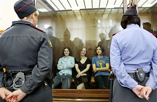 Feminist punk group Pussy Riot members, from left, Yekaterina Samutsevich, Maria Alekhina and Nadezhda Tolokonnikova sit in a glass cage in a courtroom in Moscow today. The women, two of whom have young children, were found guilty of