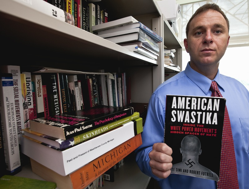 """Pete Simi holds his book """"American Swastika"""" while posing for a photo in his office in Omaha, Neb., Tuesday, Aug. 7, 2012. Simi, a professor at the School of Criminology and Criminal Justice at the University of Nebraska-Omaha, has done extensive field research into domestic hate groups, white supremacists and neo-Nazis. He knew Wade Michael Page, the Wisconsin Sikh temple gunman, from field research he did in southern California in 2001-2003 but had since lost touch with him. (AP Photo/Nati Harnik)"""