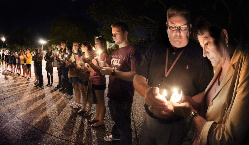 "In this Monday, Aug. 13, 2012 photo, Texas A&M chief of police Elmer Schneider, right, gives his wife Dee Ann a flame from his candle during the candlight vigil on the Texas A&M campus in College Station, Texas. Police said Tuesday that 35-year-old Thomas Alton Caffall III had ""long guns and pistols"" in his home when Brazos County Constable Brian Bachmann showed up to deliver an eviction notice. Officials say Bachmann was fatally wounded as he approached the home and a bystander died in the shootout. Caffall died at a hospital. (AP Photo/Bryan-College Station Eagle, Dave McDermand)"
