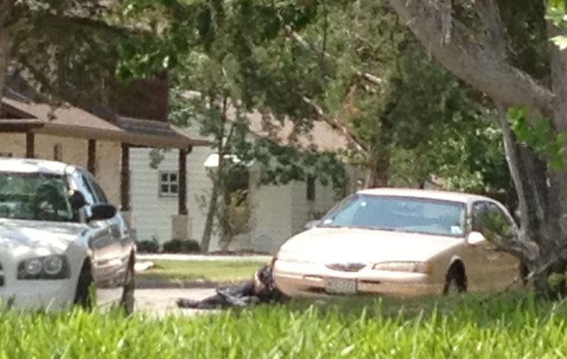 In this Aug. 13, 2012 photo provided by Rigo Cisneros, an officer takes cover, center, behind a vehicle during a shooting at a house in College Station, Texas, near Texas A&M University. Brazos County constable Brian Bachmann, a veteran of 19 years, was making what was supposed to be a routine house call to serve an eviction notice at the property when the recipient, Thomas Alton Caffall, opened fire and shots were exchanged. Bachmann, Caffall and another man were killed by the gunfire. (AP Photo/Rigo Cisneros)