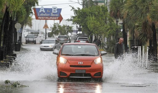 A car goes through a flooded street due to heavy rains in Key West, Fla., Sunday as heavy winds and rain hit the northern coast.