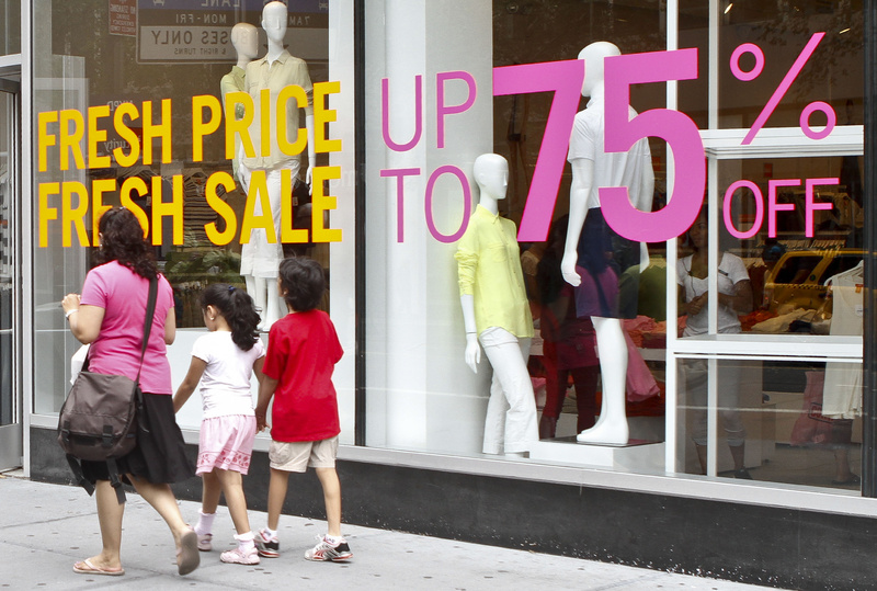 Shoppers in New York pass signs for discounted clothing sales in July. U.S. retail sales rose in July by the largest amount in five months, the Commerce Department reported Tuesday.