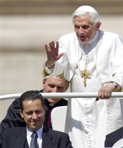 Pope Benedict XVI delivers his blessing as he arrives at St. Peter's square at the Vatican for a general audience in this May, 23, 2012, photo. His personal butler Paolo Gabriele is at lower left.