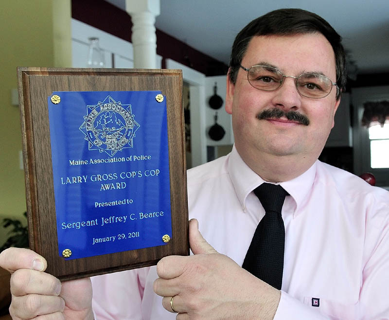 Waterville police Sgt. Jeffrey Bearce holds the Larry Gross Cop's Cop Award he received in February 2011. The state's human rights panel says Bearce was subject to illegal workplace discrimination.