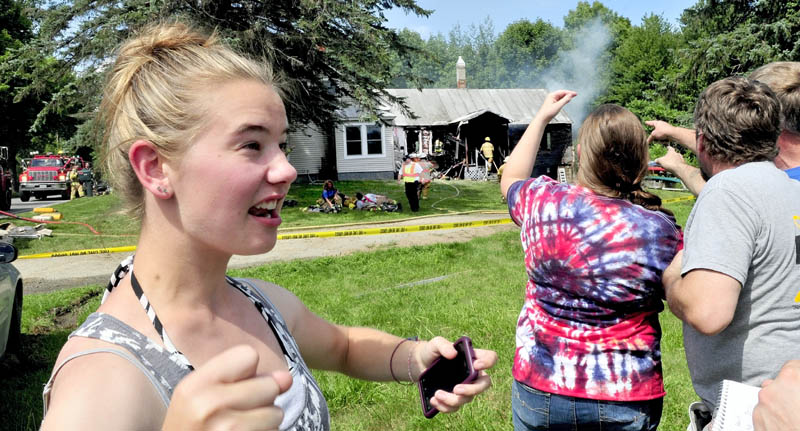 Babysitter Amanda Garboski recounts her reaction after discovering fire in this home on the Smithfield Road in Belgrade on Monday. Angelia and Kevin Tozier point as firefighters extinguish the stubborn blaze. Garboski got two children and a dog out safely.
