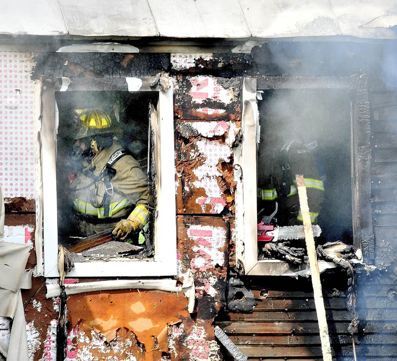 Staff photo by David Leaming SERIOUS DAMAGE: Firefighters search for fire inside a home that caused serious damage to the building on the Smithfield Road in Belgrade on Monday.