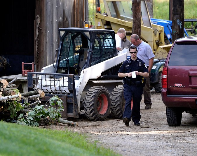 Officer Benjamin Davis of the Cape Elizabeth Police Department leaves the scene of his investigation of an explosion at a residence in Cape Elizabeth off Harvest Lane on Wednesday. One man was injured and taken to the hospital.