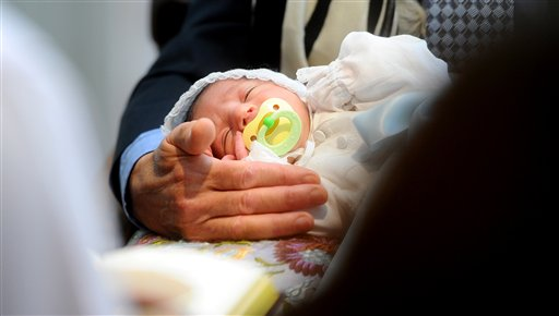 In a 2011 file photo, Benjamin Abecassis closes his eyes during his bris, a Jewish circumcision ceremony, in San Francisco. The American Academy of Pediatrics, which represents pediatricians across the Unted States, has released a policy statement that says the health benefits of male circumcision far outweigh any risks it might offer.