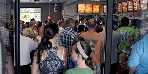 """Customers wait on line at a packed Chick-fil-A in Myrtle Beach, S.C. during lunch, Wednesday, Aug. 1, 2012. Supporters of Chick-fil-A are planning to eat at restaurants in the chicken chain as the company continues to be criticized for an executive's comments about gay marriage. Former Arkansas Gov. Mike Huckabee, a Baptist minister, declared Wednesday national """"Chick-fil-A Appreciation Day."""" Opponents of the company's stance are planning """"Kiss Mor Chiks"""" for Friday, when they are encouraging people of the same sex to show up at Chick-fil-A restaurants around the country and kiss each other. (AP Photo/The Sun News, Charles Slate) (REV-SHARE) Chick-fil-A Appreciation Day"""