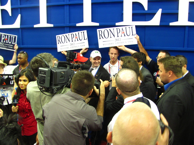 "Bernie Johnson, a Maine delegate from Lamoine wearing a white ""Ron Paul Maine 2012"" baseball hat, stands in the middle of an impromptu press conference that took place on the floor of the Republican National Convention on Monday after official business was over. Supporters of Paul from several states have been pushing for Republican officials to recognize the Texas congressman and seat more of his delegates to the convention."