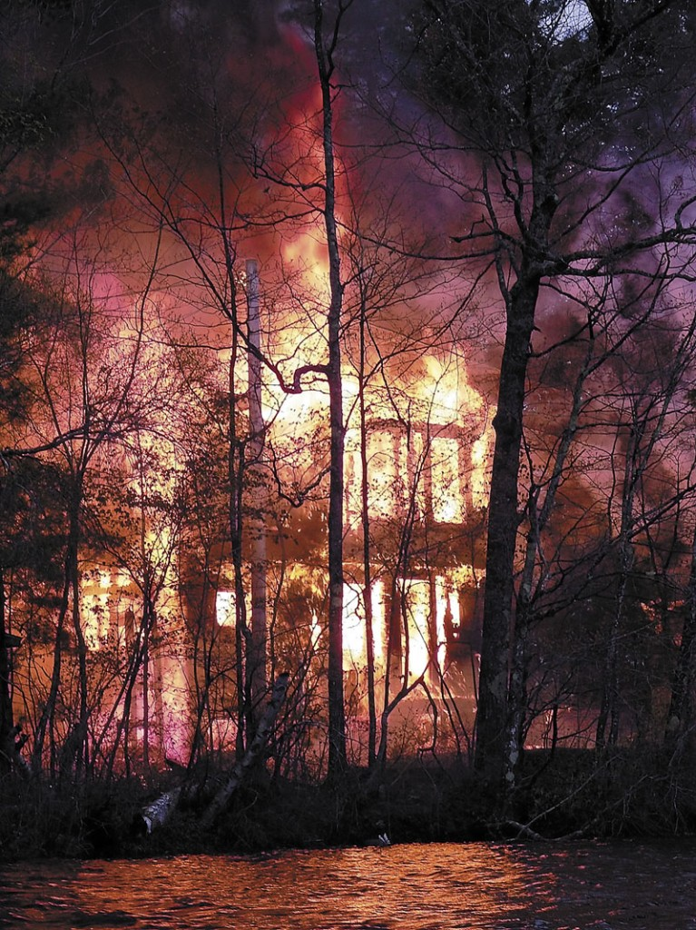 A house on Coon Island in Togus Pond goes up in flames on May 4, 2012. James Croxford has admitted setting the fire that caused an estimated $150,000 in damage.