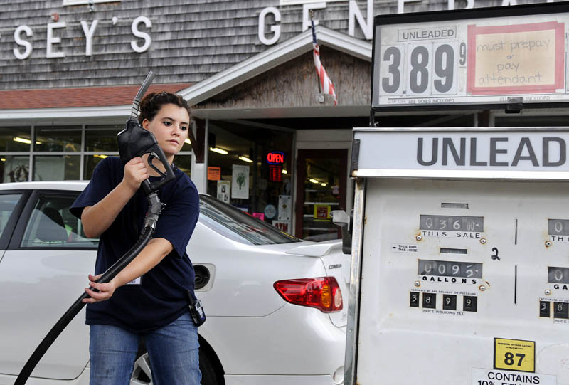 Staff photo by Andy Molloy MILEAGE: Philicity Palmer replaces a gas pump Tuesday after filling a customer's car at Hussey's General Store in Windsor. The regulations finalized Tuesday by the Obama administration require the fleet of new cars and trucks to average 54.5 miles per gallon in 13 years, up from 28.6 mpg at the end of last year.