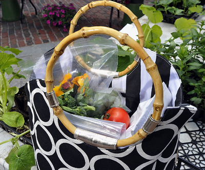A shopper at the Monument Square Farmers Market filled her shopping bag with edible flowers, herbs, greens, broccoli, stone milled flour and fresh tomatoes.
