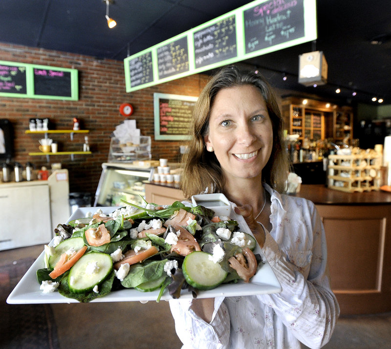 Dawn LaPointe, co-owner of The Local Buzz on Ocean House Road in Cape Elizabeth, heads toward a table to serve a customer a salad of mixed greens, cucumber, tomato and goat cheese.