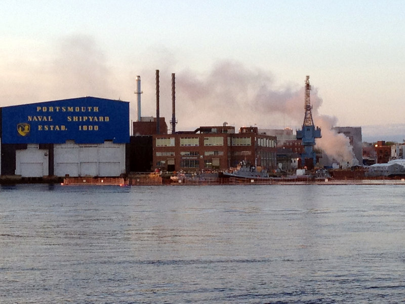 Smoke rises from the burning nuclear submarine at the Portsmouth Naval Shipyard in Kittery May 23. A civilian employee has been charged with setting a fire that caused $400 million in damage.