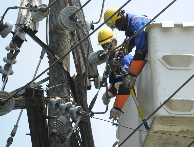 Utility workers in Springfield, Va., secure power lines on a pole as they repair lines downed by fallen trees after a severe storm in July. The biggest threat causing U.S. power failures, though, is not weather – it's weaknesses in the complex transmission grid.