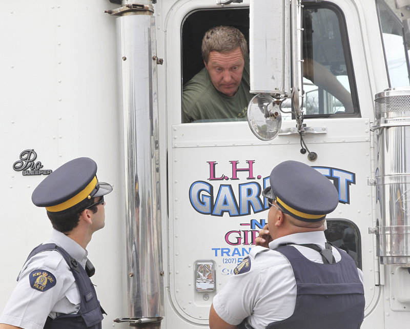 Maine truck driver Leonard Garnett of Steuben talks with police at a Shediac, New Brunswick, processing plant after fishermen blocked his truck with the intention of leaving his load of lobsters to rot.