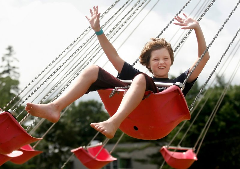 A youngster enjoys the swings at the Topsham Fair, which opens Thursday.